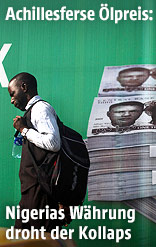 Ein Mann geht an einem Plakat mit nigerianischen Naira-Banknoten vorbei