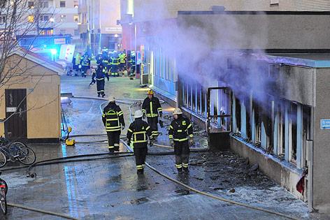Feuerwehrleute vor rauchender Moschee