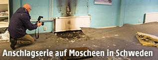 Ermittler mit Fotoapparat in einem Raum mit Brandspuren