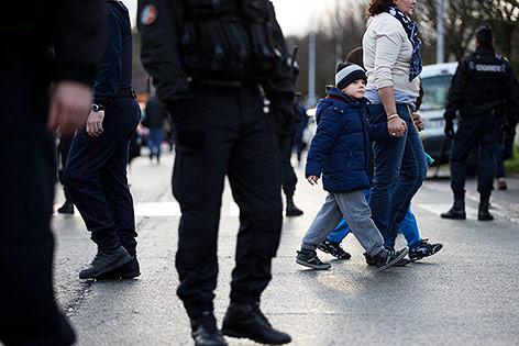 Schulkinder werden von Polizisten in Sicherheit gebracht