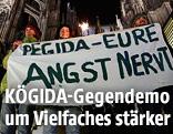 """Aktivisten der Anti-PEGIDA-Bewegung KÖGIDA halten ein Transparent mit der Aufschrift """"PEGIDA - EURE ANGST NERVT"""""""