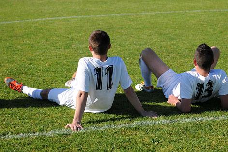 Jugendliche sitzen auf Fußballfeld