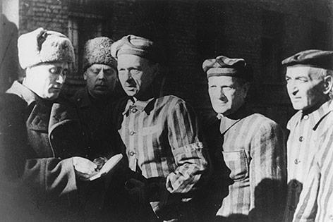 Gefangene und ein russischer Soldat im Konzentrationslager Auschwitz