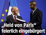 Frankreichs Innenminister Bernard Cazeneuve überreicht Lassana Bathily die Staatsbürgerschaft