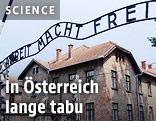 """Außenansicht des Eingangsbereichs zum nationalsozialistischen Konzentrationslager Auschwitz-Birkenau mit der Inschrift """"Arbeit macht frei"""" über dem Tor"""