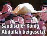 Männer tragen den in ein Tuch gewickelten verstorbenen König Abdullah auf einer Trage