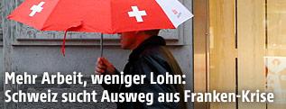 Ein Mann mit einem Regenschirm mit Design des Schweizer Wappens
