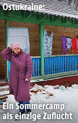 Frau steht vor einer Baracke in Romaschka