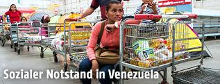 Menschen mit fast leeren Einkaufswagen stehen Schlange in einem Supermarkt