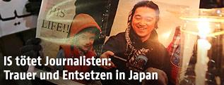Bild vom getöteten Journalisten Kenji Goto neben einer Kerze