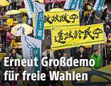 Demonstranten mit gelben Regenschirmen