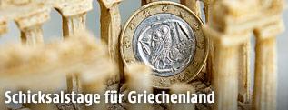 Eine griechische Euromünze steht in einem Plastik-Souvenirtempel