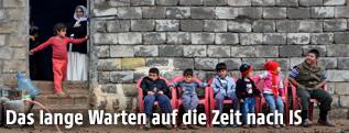 Kinder vor verfallenem Haus in Erbil