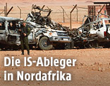 Algerischer Soldat vor zerstörten Fahrzeugen