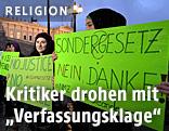 Menschen demonstrieren gegen das Islamgesetz