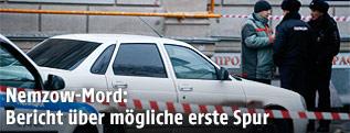 Polizisten neben Auto hinter Absperrung