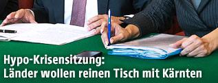 Hände, Kugelschreiber und Unterlagen auf einem Verhandlungstisch