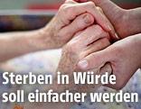 Pflegerin hält Hände einer Patientin