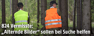 Feuerwehrleute mit Warnwesten suchen im Wald