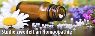 Geöffnete Flasche mit homöopathischen Globuli neben Blumen