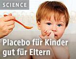 Eine Hand hält einem Kleinkind einen Plastiklöffel hin