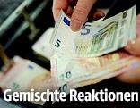 Geldscheine werden in eine Registrierkasse gelegt