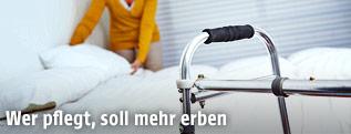 Frau richtet ein Bett, im Vordergrund steht ein Rollator