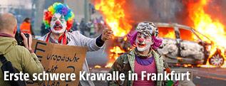 Demonstranten im Clown-Kostüm vor einem brennenden Auto
