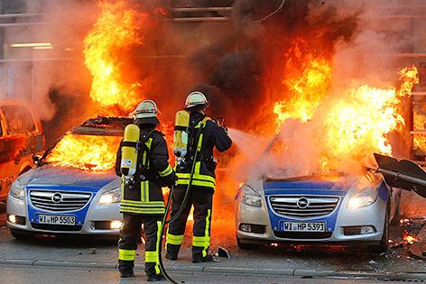 Feuerwehrmänner löschen brennende Autos