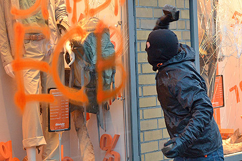 Ein Demonstrant schlägt gegen eine Fensterscheibe