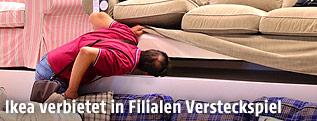 Ein Mann schaut in einer Ikea-Filiale unter ein Sofa