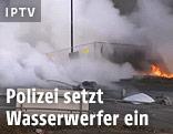 Wasserwerfer und brennendes Auto