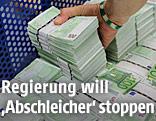 Eine Hand greift nach einem Stapel 100-Euro-Scheine
