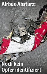 Ermittler untersucht ein Wrackteil des Flugzeugs