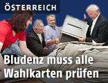 Wahlhelfer entleeren eine Wahlkartenbox