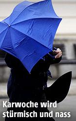 Frau mit Regenschirm bei stürmischem Wetter