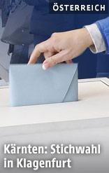 Person wirft eine Wahlkarte in eine Urne