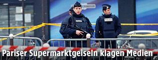 Polizisten vor einem abgesperrten Supermarkt