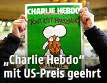 """Eine Person hält ein """"Charlie Hebdo""""-Cover hoch"""