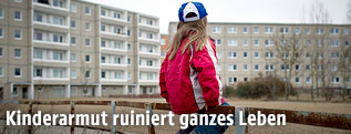 Ein kleines Mädchen sitzt auf einem rostigen Geländer im Innenhof eines Wohnbaus