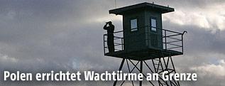Person mit Feldstecher auf einem Wachturm