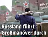 Ein Mann trägt eine Luft-Boden-Rakete neben Kampfflugzeugen