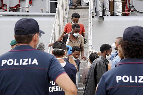 Afrikanische Migranten verlassen unter Polizeiaufsicht ein Boot der italienischen Marine