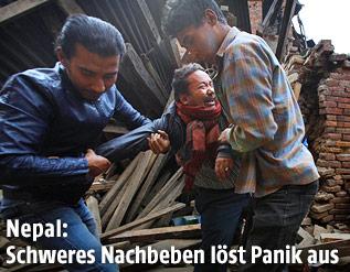 Zwei Männer tragen einen weinenden Mann aus einem zerstörten Haus