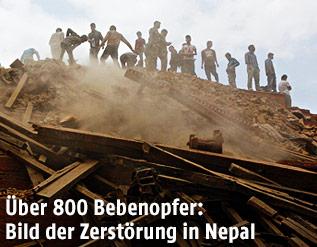Menschen suchen in den Trümmern eines eingestürzten Gebäudes nach Verschütteten
