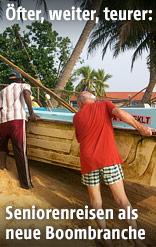 Ein Tourist schiebt auf Sri Lanka mit Einheimischen ein Boot aus dem Wasser