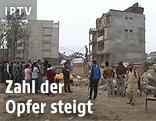 Menschen vor Trümmern