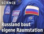 Astronaut mit russischer Flagge auf dem Arm