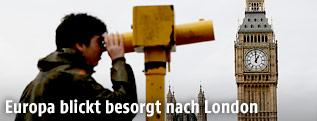 Ein Mann sieht gegenüber des britischen Parlaments durch ein Teleskop
