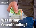 Eine Person hält Euro-Scheine in der Hand